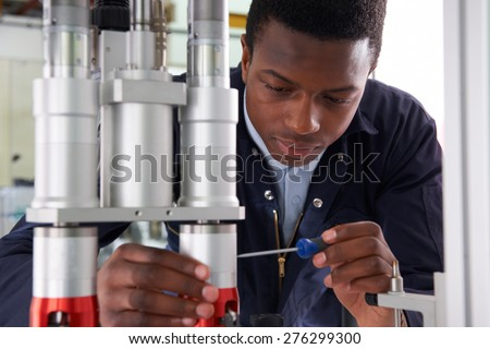 Male Apprentice Engineer Working On Machine In Factory - stock photo