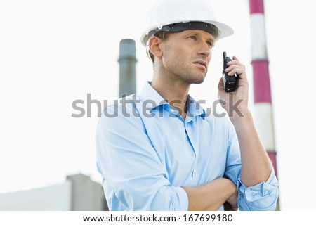 Male architect communicating on two way radio at site - stock photo