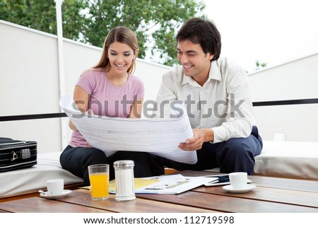 Male architect discussing house plans with female - stock photo