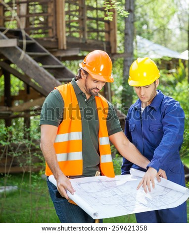 Male architect explaining blueprint to colleague at construction site - stock photo