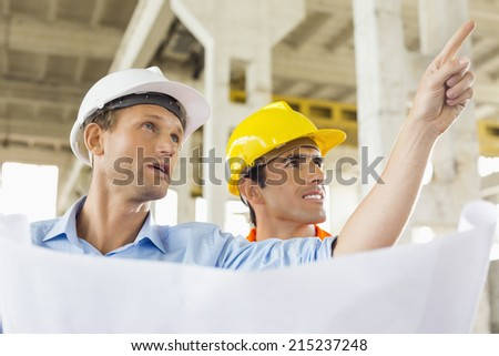 Male architect explaining building plan to colleague at construction site - stock photo