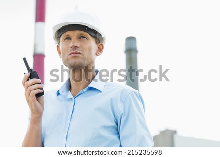 Male architect holding walkie-talkie at site - stock photo