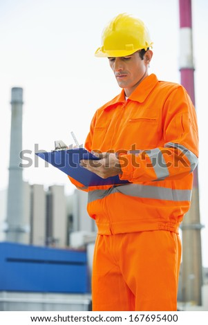 Male architect in protective workwear writing on clipboard at site - stock photo