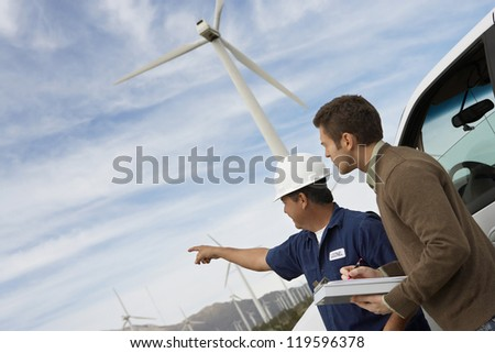 Male architect pointing towards something with foreman noting down the plan - stock photo