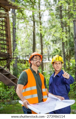 Male architect showing something to colleague holding blueprint at construction site - stock photo