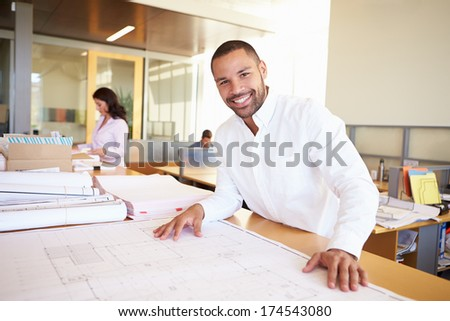 Male Architect Studying Plans In Office - stock photo