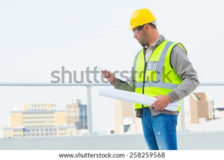 Male architect with blueprints reading clipboard outdoors - stock photo