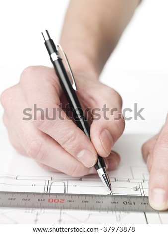 Male architect working on a blueprint, close up on hand and blueprint.