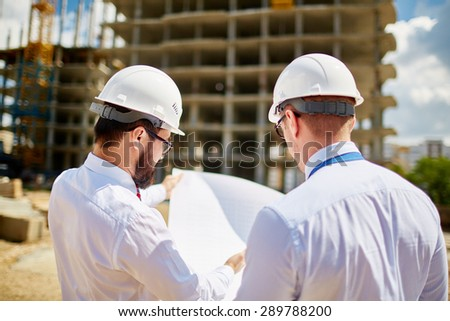 Male architects in helmets discussing sketch of new building