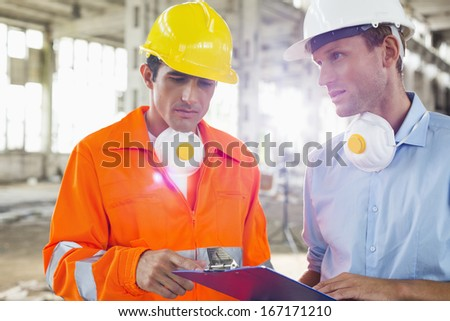 Male architects in protective workwear discussing at construction site - stock photo