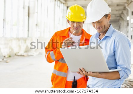 Male architects using laptop at construction site - stock photo