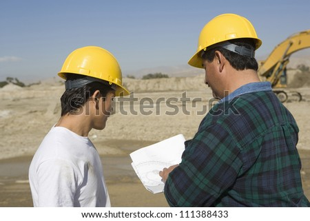 Male architects wearing hard hat at construction site