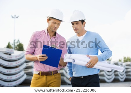 Male architects with blueprint and clipboard working at site - stock photo