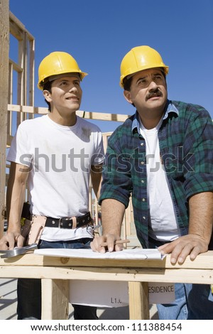 Male architects with blueprint at a construction site - stock photo