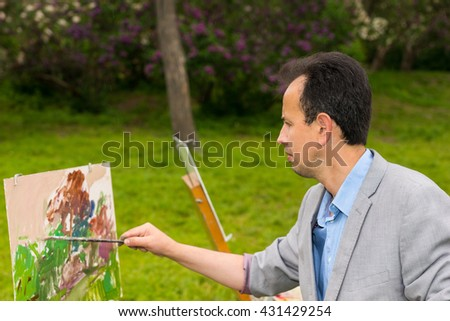 Male artist during creation a masterpiece on a trestle and easel painting with oils and acrylics in a park - stock photo