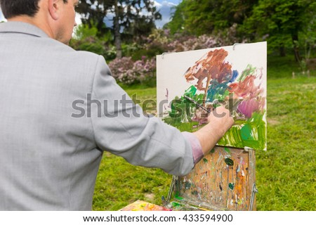 Male artist painting a standing in front of  a sketchbook during creation a beautiful sketch of picture outdoors - stock photo