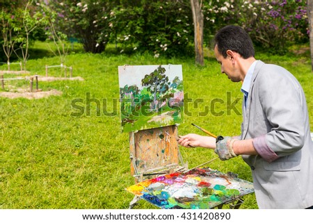 Male artist painting outdoors in the park  on a trestle and easel painting with oils and acrylics holding paintbrush and paletteknife wearing a glove - stock photo