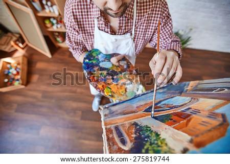 Male artist painting Venetian street - stock photo