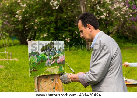 Male artist working on a trestle and easel wearing a glove painting with oils and acrylics  outdoors painting a garden scene with flowers - stock photo