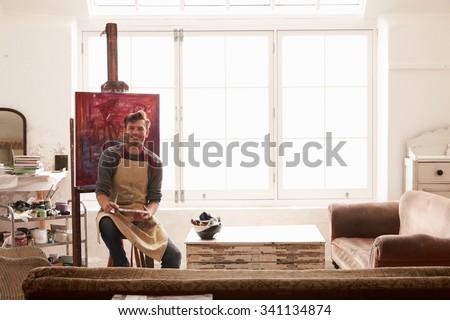 Male Artist Working On Painting In Bright Daylight Studio - stock photo