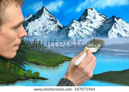 Male artist working with concentrated expression on a beautiful blue landscape painting - stock photo