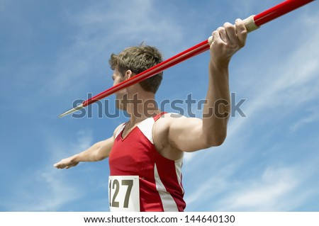 Male athlete about to throw javelin against the sky - stock photo