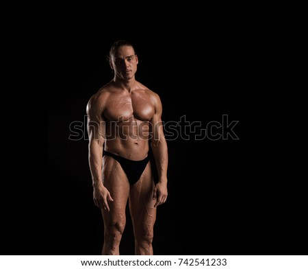 Male athlete bodybuilder posing on a black background