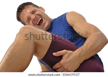 Male athlete clutching his hamstring in excruciating pain on white background