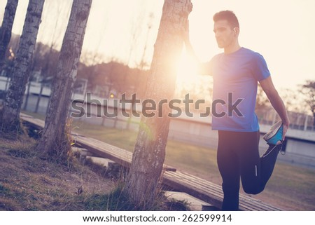 Male athlete doing stretching muscles for running in the park at sunset (intentional sun glare and vintage color) - stock photo
