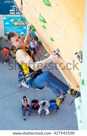 Male Athlete hanging on climbing Wall of national Competitions with very emotional Face. Dnipro, Ukraine, May 20, 2016 - stock photo