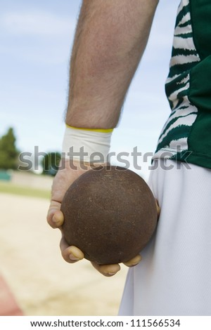 Male athlete holding metal ball on track and field - stock photo