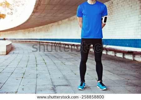 male athlete in blank t-shirt standing outdoors - stock photo