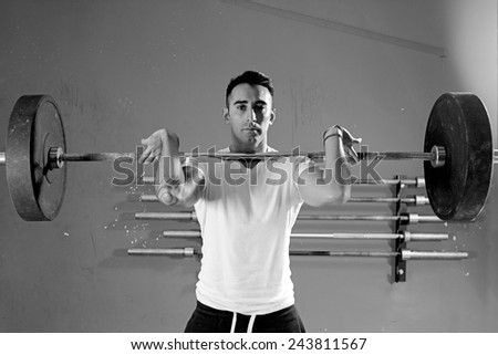 male athlete is lifting a barbell at the gym - focus on the man