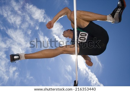 Male athlete jumping over hurdle, view from below - stock photo
