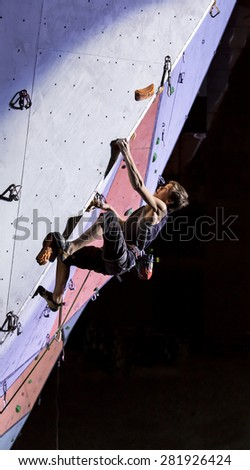 Male athlete makes hard move on climbing wall. National Climbing Championship, Lead climbing finals. Dnepropetrovsk, Ukraine, May 23, 2015