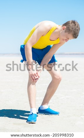 Male athlete on floor clutching knee and hamstring in excruciating pain on white background - stock photo