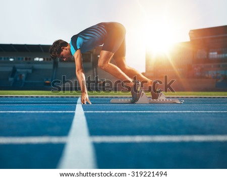 Male athlete on starting position at athletics running track. Runner practicing his sprint start in athletics stadium racetrack. - stock photo