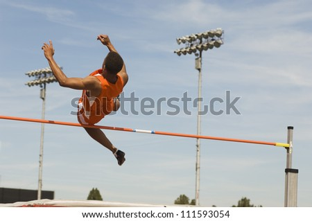 Male athlete performing high jump against sky - stock photo