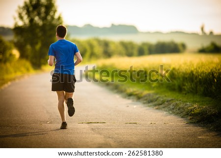 Male athlete/runner running on road - jog workout well-being concept - stock photo