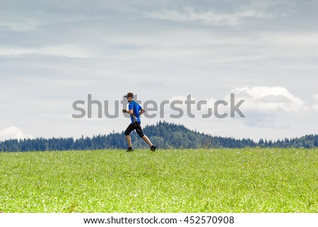 Male athlete running through the fields at mountains background