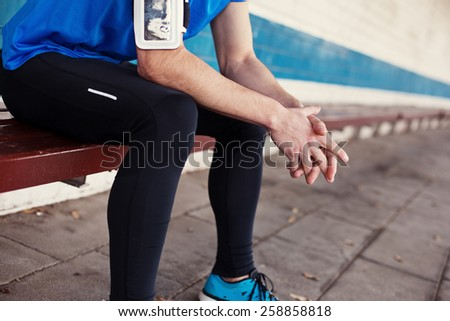 male athlete sitting and resting on the bench - stock photo
