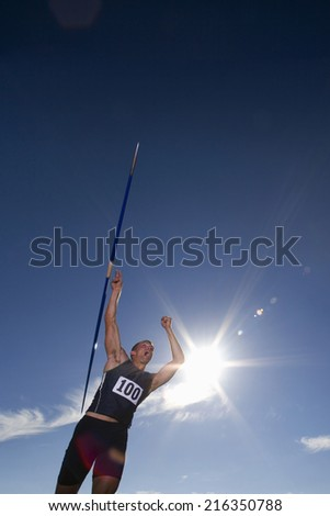 Male athlete throwing javelin, low angle view (lens flare) - stock photo
