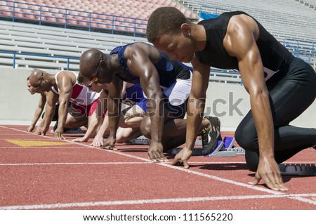 Male athletes at starting line in track race
