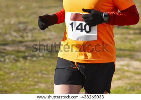 Male athletic runner on a cross country race. Outdoor circuit. Horizontal
