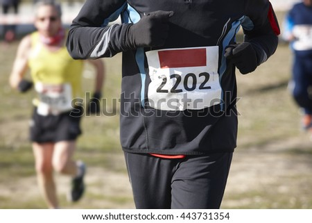 Male athletic runners on a cross country race. Outdoor circuit. Horizontal
