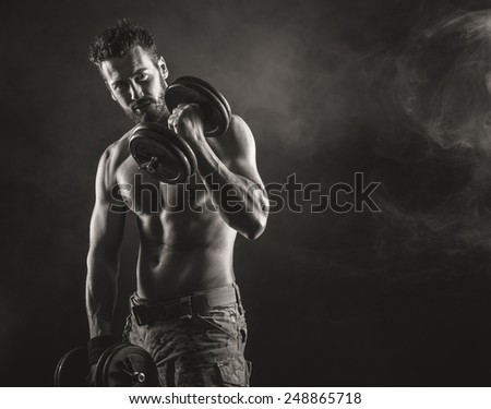 Male attractive body builder working out with dumbbells, strength and fitness concept - stock photo