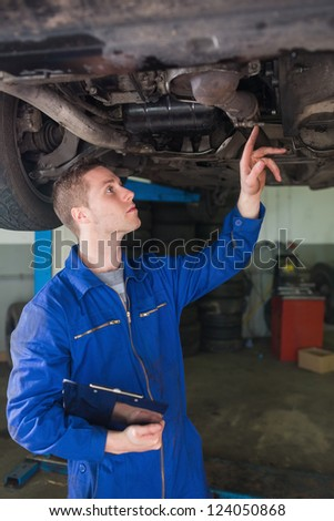 Male auto mechanic with clipboard examining under car in workshop - stock photo