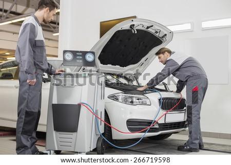 Male automobile mechanics examining car in repair shop - stock photo
