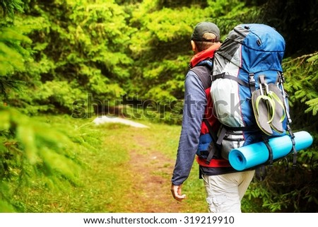 Male backpacker hiking/tracking through mountain forest. - stock photo