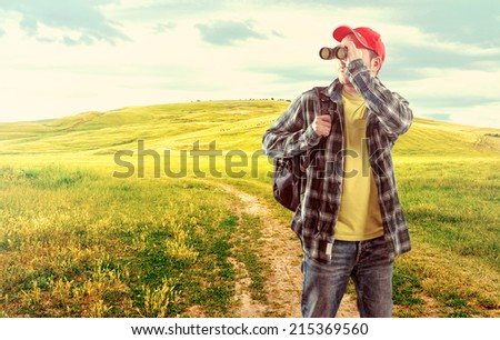 Male backpacker in cap looking in binocular over green meadow background. Young man hiker traveling through countryside.  - stock photo